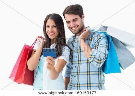 Attractive young couple with shopping bags and credit card on white background
