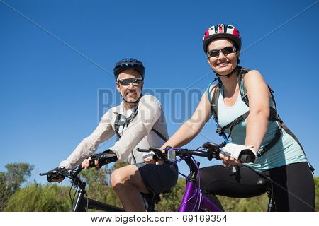 Active happy couple going for a bike ride in the countryside on a sunny day
