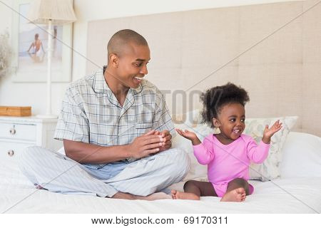 Happy father and baby girl sitting on bed together at home in the bedroom