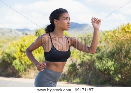 Fit woman running along the open road on a sunny day in the countryside