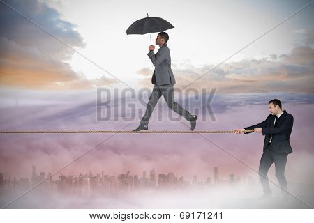 Young businessman pulling a tightrope for business man against cityscape in the clouds