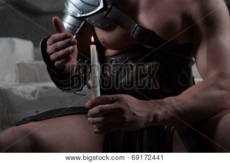 Gladiator in armour sitting on steps of ancient temple holding c