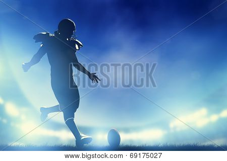 American football player kicking the ball, kickoff. Night stadium lights