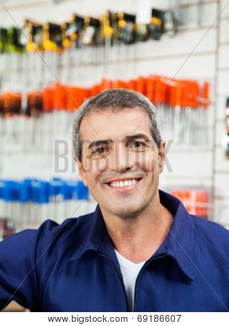 Portrait of mature male worker smiling in hardware shop