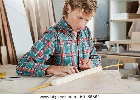 Mid adult carpenter measuring wood at table in workshop