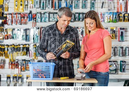 Man and woman making payment through smartphone in hardware store