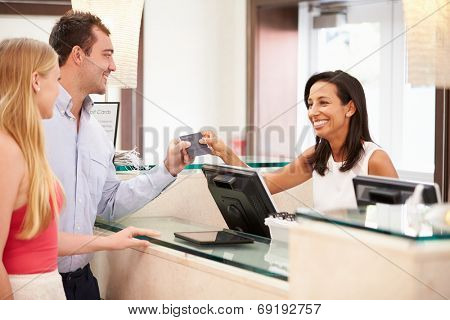 Couple Checking In At Hotel Reception