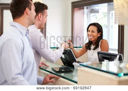 Male Couple Checking In At Hotel Reception