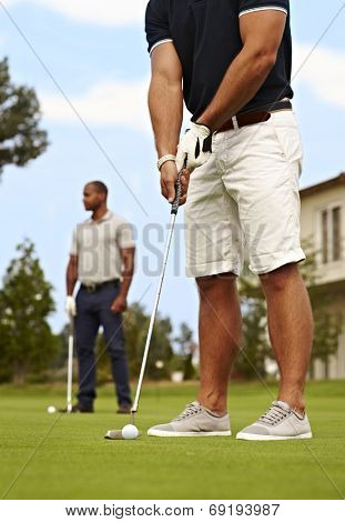 Male golfer ready for holing, standing on the green.