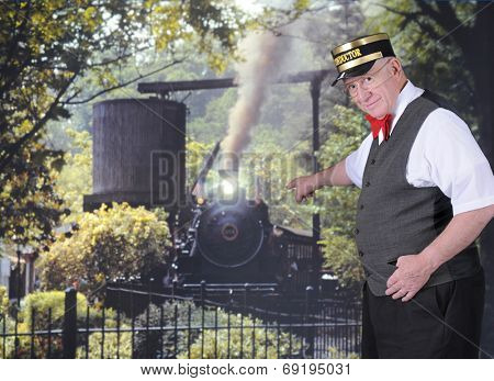 A senior adult conductor point to a coming train while looking at the viewer.
