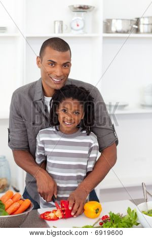 Smiling Father Helping His Son Cut Vegetables