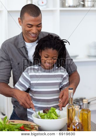 Adorable Little Boy Preparing Salad With His Father