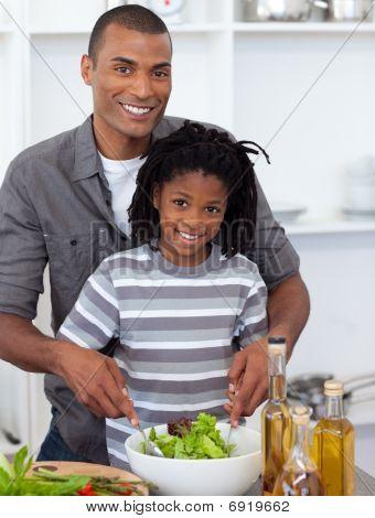 Sonriente a niño preparar ensalada con su padre
