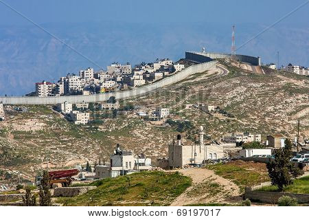 Small village and palestinian town on the hill behind separation wall on the West Bank in Israel.