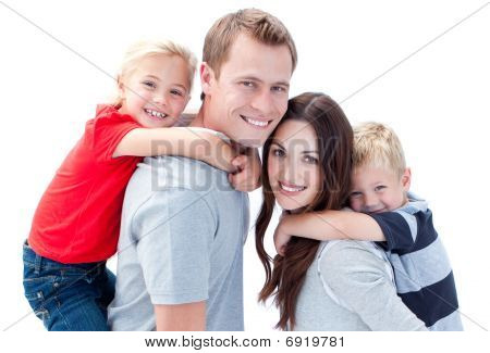 Portrait Of Joyful Family Enjoying Piggyback Ride Against A White Background