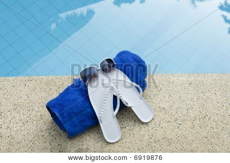 Sunglasses, Shoes And Towel On Edge Of Pool With Blue Water