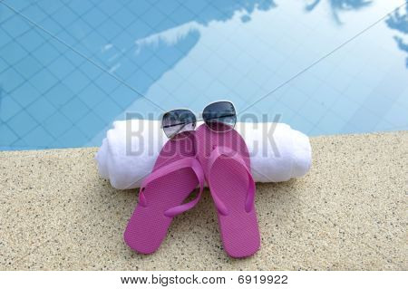 Pink Shoes With White Towel And Sunglasses On Edge Of Pool With