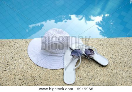 White Hat , Shoes And Sunglasses Next To Pool With Calm Blue Wat