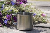 foto of ferrous metal  - Tourist metal cup next to the flowers stands on a gray wooden table - JPG