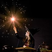 picture of dress-making  - Little Halloween witch making magic with stick - JPG