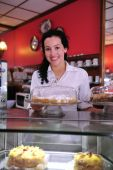 foto of grocery store  - owner of a small business/ cake store/ cafe showing her tasty cakes