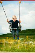 stock photo of swingset  - Little blonde boy having fun at the playground - JPG