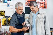 stock photo of hardware  - Portrait of senior salesman accepting payment through NFC technology from male customer in hardware store - JPG