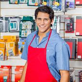 stock photo of hardware  - Portrait of handsome young salesman in red apron smiling at hardware shop - JPG