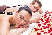 foto of hot couple  - Portrait of attractive couple relaxing in spa salon with hot stones on body - JPG