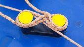 pic of bollard  - Twisted orange rope round a yellow bollard large ship - JPG