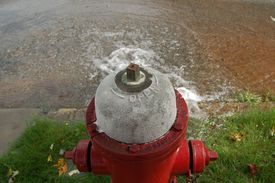 foto of gushing  - A fire hydrant gushing water into a city street - JPG