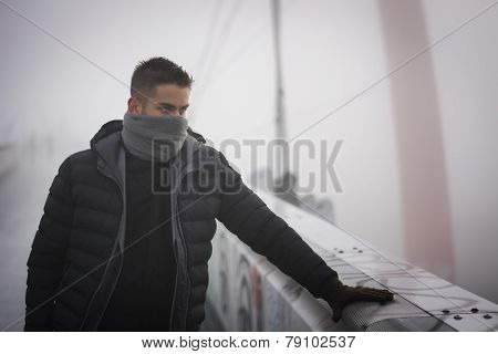 Young man in winter fashion standing outdoors with scarf hiding his face