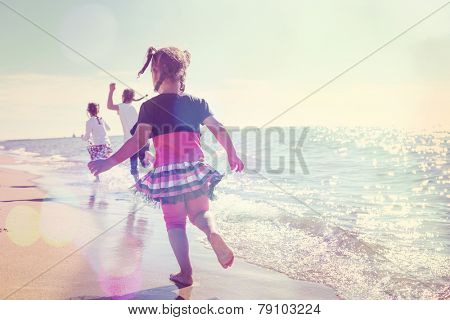 Children running on the beach in the waves