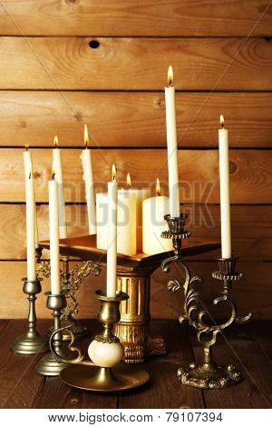 Retro candlesticks with candles on wooden background