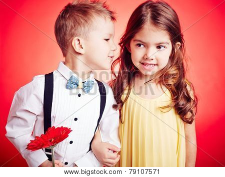 Cute little boy whispering something to his girlfriend