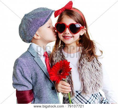 Portrait of well-dressed children, boy kissing a girl
