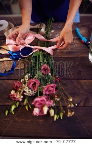 Florist decorating rose bouquet with ribbon
