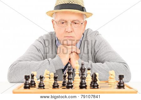 Senior contemplating his next move in game of chess isolated on white background