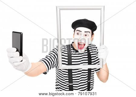 Mime artist taking selfie behind a picture frame isolated on white background