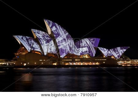 Sydney Opera with festival graphics lighting.