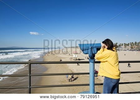 A tourist on the Huntington Beach pier watches surfers through coin operated binoculars during a bright, sunny day. T
