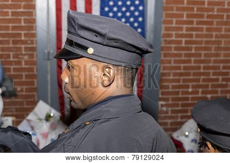 NYPD officer waits to light candle