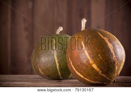 Pumpkins on aged wooden background