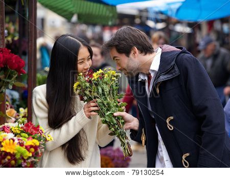 Happy Couple Smelling Flowers Together