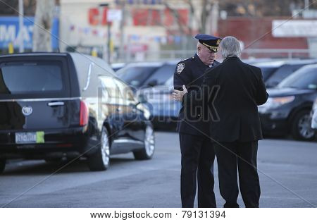 NYPD officers with hearse in background