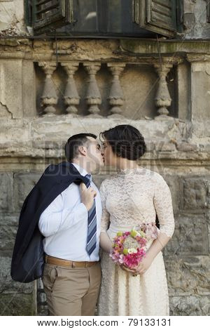 Young wedding couple kissing on the street