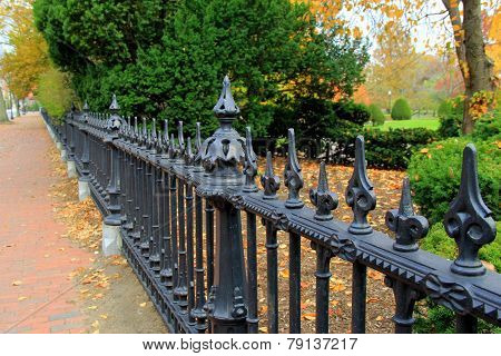 Black wrought-iron fence and brick walkway
