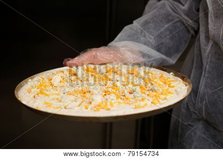 Raw four cheeses pizza in chef's hand