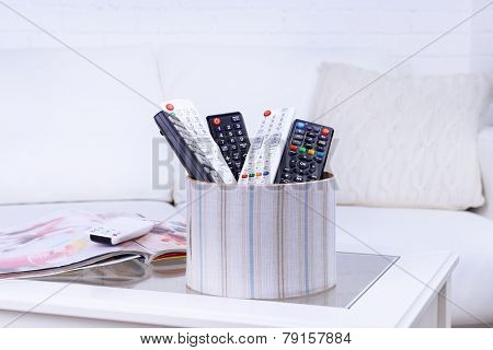 Many remote control devices on table in room