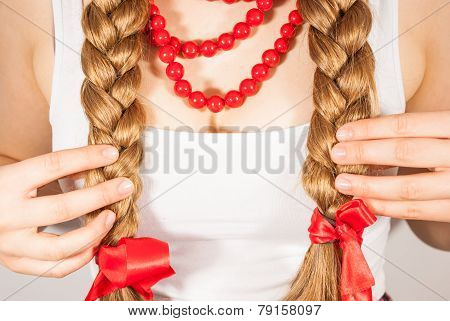 A young beautiful girl with long tresses wearing red corals